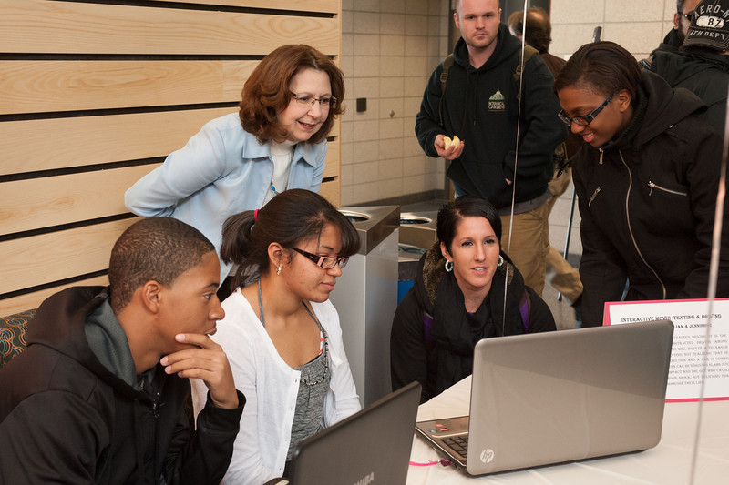 A group of students around a laptop