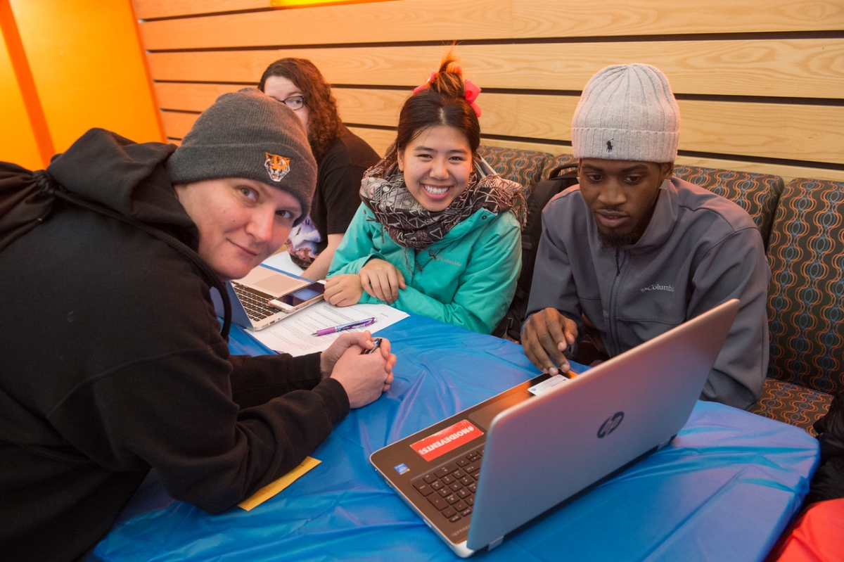 Four students looking at a laptop